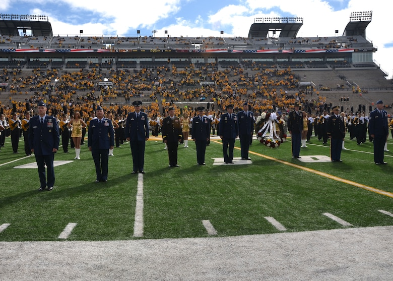 Military leadership and National Adopt A Warrior honorees take their places on the football field for a ceremony at the University of Missouri in Columbia, Oct. 3, 2015.  The servicemen and women were honored prior to the game as part of Military Appreciation Day.  (U.S. Air National Guard photo by Tech. Sgt. Traci Howells)