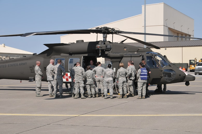 Crew chiefs from the Montana Army National Guard's 1-189th Aviation Battalion instruct Airmen from the 341st and 120th Medical Groups on how to load litters into an H-60 Blackhawk helicopter during a mass casualty exercise Aug. 10, 2015, at Malmstrom Air Force Base, Mont. The exercise tested the units' abilities to jointly respond to a mass casualty event resulting from a natural disaster. (U.S. Air National Guard photo/ Tech. Sgt. Michael Touchette)