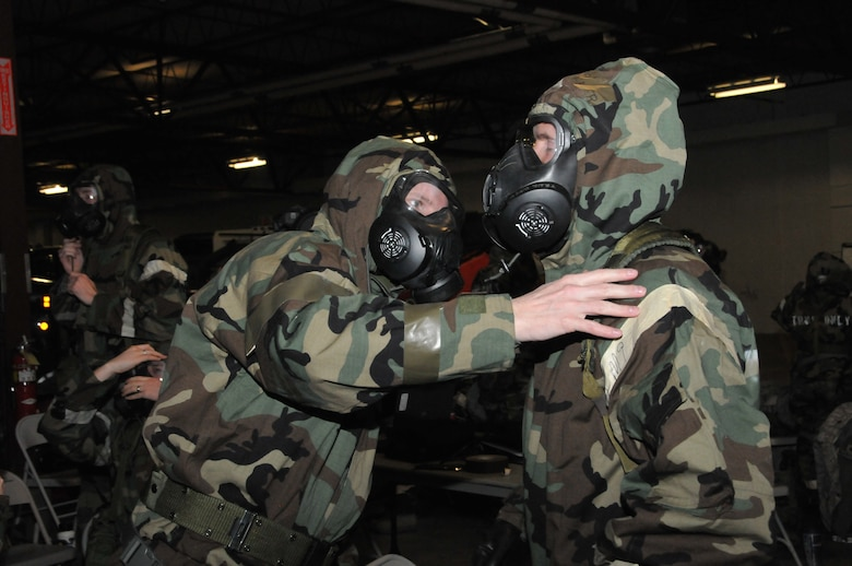 Airman of the Montana National Guard check over the ties and snaps of their chemical warfare gear in the unit's cold storage building during expeditionary skills rodeo training Feb. 7, 2015. (U.S. Air National Guard photo/Tech. Sgt. Christy Mason)
