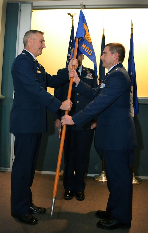 Col. Howard Eissler, 111th Attack Wing commander, hands the medical group's flag to newly-appointed 111th Medical Group Commander Lt. Col. Scott Coradi Oct. 3, 1025, Horsham Air Guard Station, Pennsylvania. Lt. Col. John p. Quinn Jr., the outgoing commander, served in the position since 2009. (U.S. Air National Guard photo by Tech. Sgt. Andria Allmond/Released)