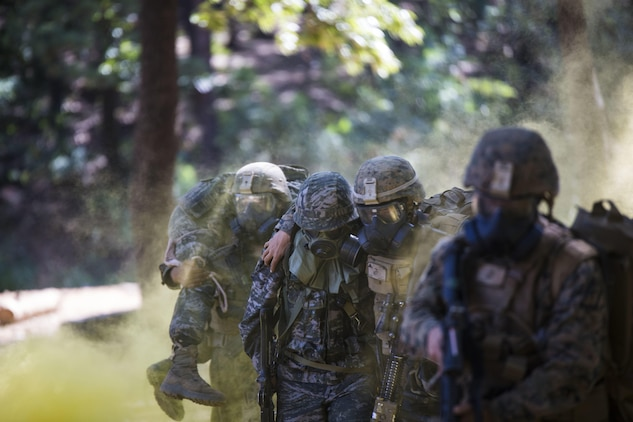Republic of Korea Marine Lance Cpl. Jun Shin, center, supports a U.S. Marine moving to safety during a gas attack drill as part of Korean Marine Exchange Program 15-12 at Gunha-Rhi, Republic of Korea, Sept. 17, 2015. The drill was part of KMEP 15-12, an exercise that enhances the ROK and U.S. alliance, promotes stability on the Korean Peninsula and strengthens ROK and U.S. military capabilities and interoperability. Shin is with 2nd Company, 11th Battalion, 1st Regiment, 2nd Marine Division, ROK Headquarters Marine Corps. The U.S. Marines are with Fox Company, 2nd Battalion, 3rd Marine Regiment, currently supporting 3rd Marine Division under the unit deployment program.
