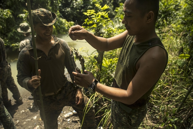 Philippine Marine Corps Cpl. Elmer Addatu, right, grabs a fish of the line of U.S. Marine Corps Cpl. Lucas Fernandez's improvised fishing pole during jungle survival training at Ternate, Philippines, Sept. 30, as part of Amphibious Landing Exercise 2015. The Marines learned basic jungle survival skills, such as building a fire, finding sources of fresh water and catching food. PHIBLEX 15 is an annual, bilateral training exercise conducted by U.S. Marine and Navy Forces with the Armed Forces of the Philippines in order to strengthen our interoperability and working relationships across the range of military operations — from disaster relief to complex expeditionary operations. Addatu is a reconnaissance man with 64th Force Recon Company, Marine Special Operations Group. Fernandez from Greenwich, Connecticut, is a reconnaissance man with 3rd Recon Battalion, 3rd Marine Division, III Marine Expeditionary Force.