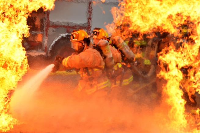 Air Force firefighters rush into extreme-heat temperatures to extinguish a fire during training in Garden City, Ga., Oct. 3, 2015. The firefighters are assigned to the Georgia National Guard's 165th Airlift Wing Fire Emergency Services Flight. Georgia National Guard photo by Air Force Staff Sgt. Noel Velez
