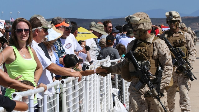 Marines assigned to 1st Marine Division shake hands with audience members during the 2015 Air Show's Marine Air-Ground Task Force demonstration at Marine Corps Air Station Miramar, Calif., Oct. 2. The MAGTF demonstrated the capabilities of several air and ground Marine Corps assets.