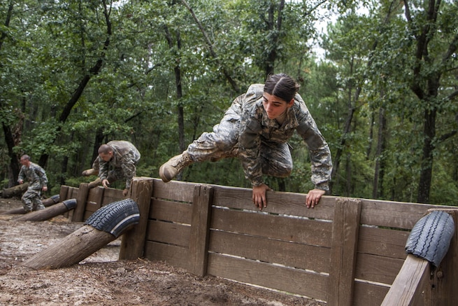 Army Pvt. Vanessa DaSilva leads her squad over the low wall of the Fit to Win Endurance course on Fort Jackson, S.C., Oct. 1, 2015. DaSilva, who is in her second week of basic combat training, is assigned to Company B, 3rd Battalion, 34th Infantry Regiment. U.S. Army photo by Sgt. 1st Class Brian Hamilton