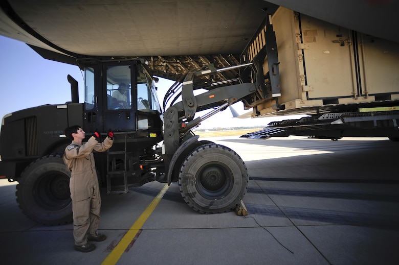 Senior Airman Ashley Igulo, a 14th Airlift Squadron loadmaster, guides Senior Airmen Greguy Bolivar, a 435th Contingency Response Squadron air transportation journeyman, Sept. 28, 2015, during a delivery of equipment for U.S. Air Forces Central Command personnel recovery mission at Diyarbakir Air Base, Turkey. The deployment of personnel recovery assets in Turkey will enable the USAFCENT with recovery of our coalition partners should they need assistance in Syria or Iraq. (U.S. Air Force photo/Airman 1st Class Cory W. Bush)