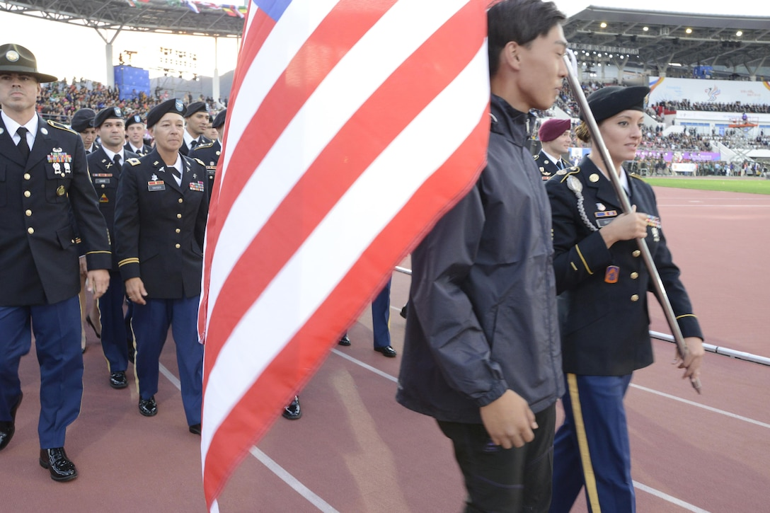 Sgt. Elizabeth Wasil carries the U.S. flag into the opening ceremony of the CISM World Games in Mungyeong, South Korea, Oct. 2, 2015. About 165 athletes and coaches follow behind her.