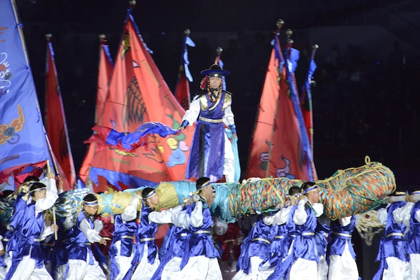 A scene of the opening ceremony of the CISM World Games depicts the traditional Korean game called Chajeon Nori. It involves teams of men carrying large log frames called dongchae. Atop each dongchae is a commander who directs his team to maneuver against the opposing team.