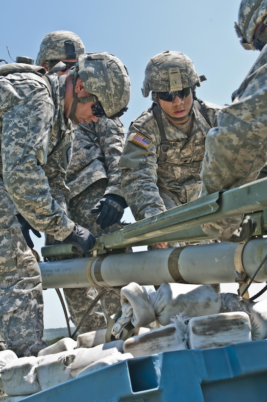 U.S. Army Reserve Soldiers with the 364th Engineer Company (Sapper) load the rocket of an M58 Mine Clearing Line Charge, a rocket-projected line charge usually used to clear mines, during River Assault at Fort Chaffee, Ark., July 29. (U.S. Army photo by Staff Sgt. Roger Ashley)