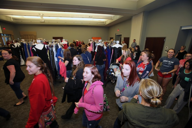 Spouses of active-duty Marines rush in to select a free ball gown during Operation Ball Gown at Marine Corps Air Station Cherry Point, N.C., Oct. 2, 2015. More than 100 women celebrated the 7th annual Operation Ball Gown with Marine Corps Ball etiquette tips and the opportunity to select a free gown. They were given a sneak-peak into the birthday ball ceremony where they learned the ins-and-outs of the historical tradition while waiting for their opportunity to select a gown. (U.S. Marine Corps photo by Lance Cpl. Jason Jimenez/Released)