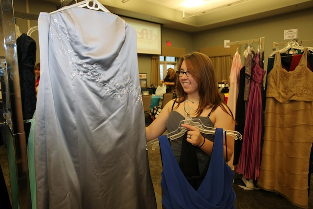 Rachel Jones selects a gown during Operation Ball Gown at Marine Corps Air Station Cherry Point, N.C., Oct. 2, 2015. More than 100 women celebrated the 7th annual Operation Ball Gown with Marine Corps Ball etiquette tips and the opportunity to select a free gown. They were given a sneak-peak into the birthday ball ceremony where they learned the ins-and-outs of the historical tradition while waiting for their opportunity to select a gown. (U.S. Marine Corps photo by Lance Cpl. Jason Jimenez/Released)