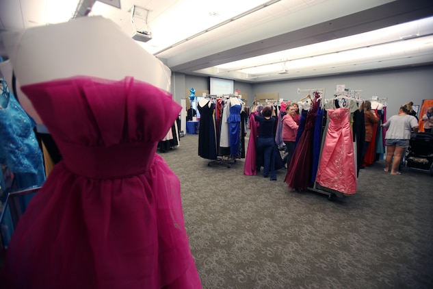 Spouses of active-duty Marines select gowns during Operation Ball Gown at Marine Corps Air Station Cherry Point, N.C., Oct. 2, 2015. More than 100 women celebrated the 7th annual Operation Ball Gown with Marine Corps Ball etiquette tips and the opportunity to select a free gown. They were given a sneak-peak into the birthday ball ceremony where they learned the ins-and-outs of the historical tradition while waiting for their opportunity to select a gown. (U.S. Marine Corps photo by Lance Cpl. Jason Jimenez/Released)