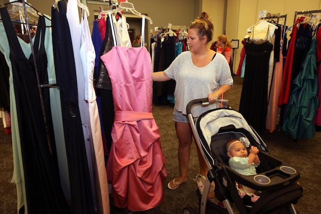 Michelle Walters selects a gown with her baby during Operation Ball Gown at Marine Corps Air Station Cherry Point, N.C., Oct. 2, 2015. More than 100 women celebrated the 7th annual Operation Ball Gown with Marine Corps Ball etiquette tips and the opportunity to select a free gown. They were given a sneak-peak into the birthday ball ceremony where they learned the ins-and-outs of the historical tradition while waiting for their opportunity to select a gown. (U.S. Marine Corps photo by Lance Cpl. Jason Jimenez/Released)
