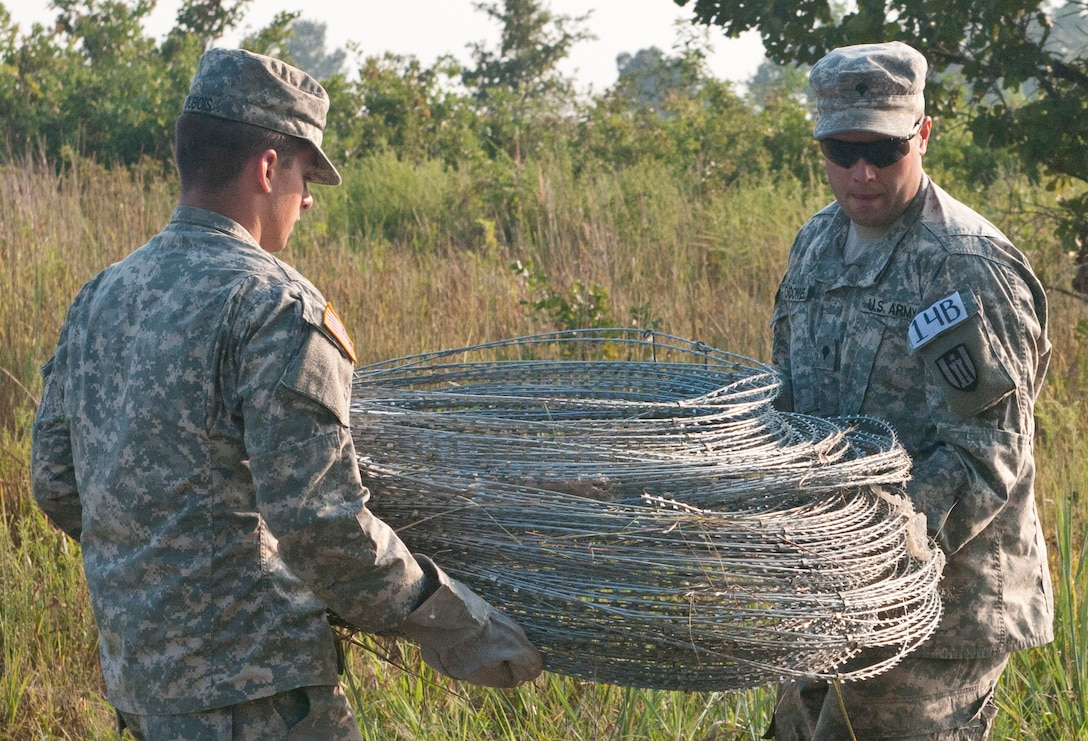 U.S. Army Reserve Spcs. Johnathan O'Connell and Jonathan Du Bois, combat engineers with the 309th Engineer Company (Mobility Augmentation), carry concertina wire to use in emplacing a hasty frat fence during Sapper Stakes 2015 at Fort Chaffee, Ark., Sept. 1. (U.S. Army photo by Staff Sgt. Debralee Best)