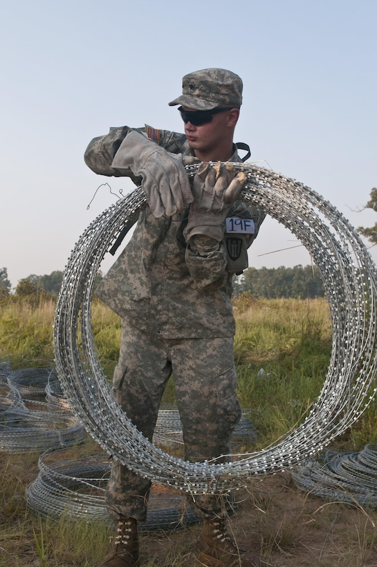 U.S. Army Reserve Spc. Tyler Chatterton, combat engineer, 402nd Engineer Company (Sapper), carries concertina wire to use in emplacing a hasty frat fence during Sapper Stakes 2015 at Fort Chaffee, Ark., Sept. 1. (U.S. Army photo by Staff Sgt. Debralee Best)