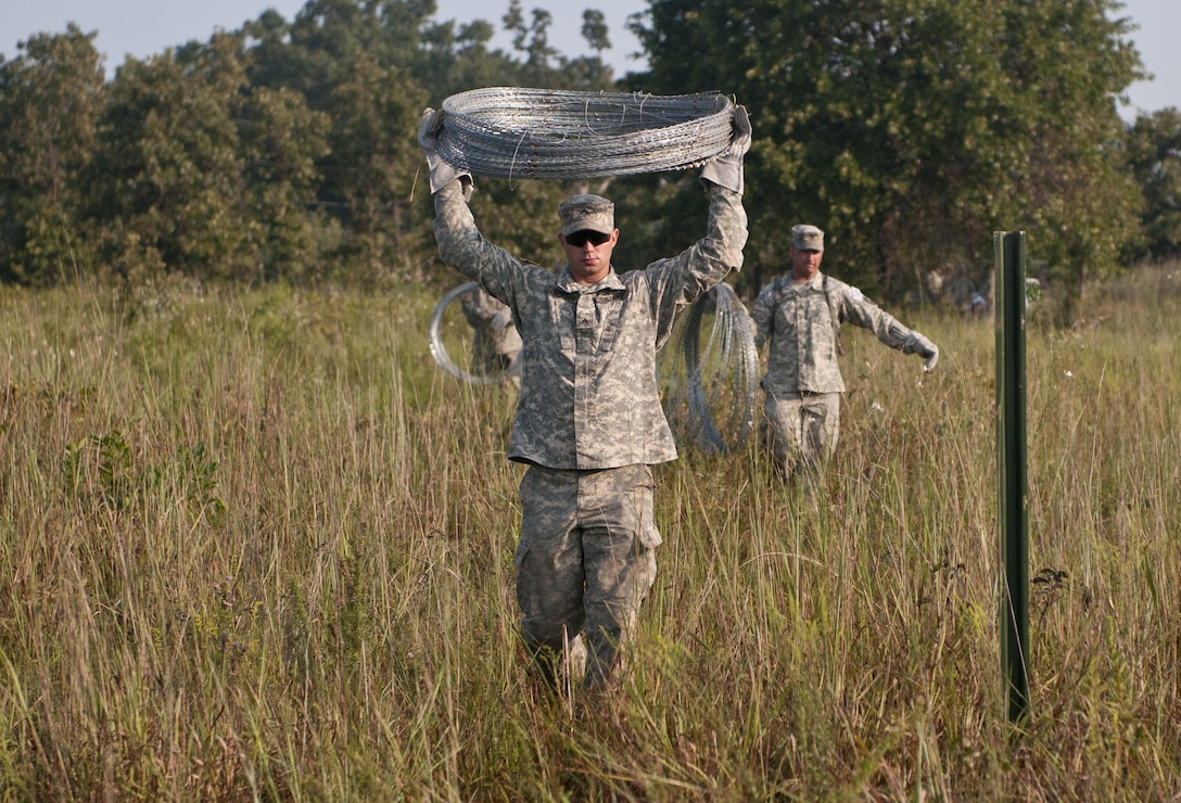 U.S. Army Reserve Cpl. Gary Coggins, combat engineer, 348th Engineer Company, carries concertina wire to use in emplacing a hasty frat fence during Sapper Stakes 2015 at Fort Chaffee, Ark., Sept. 1. (U.S. Army photo by Staff Sgt. Debralee Best)