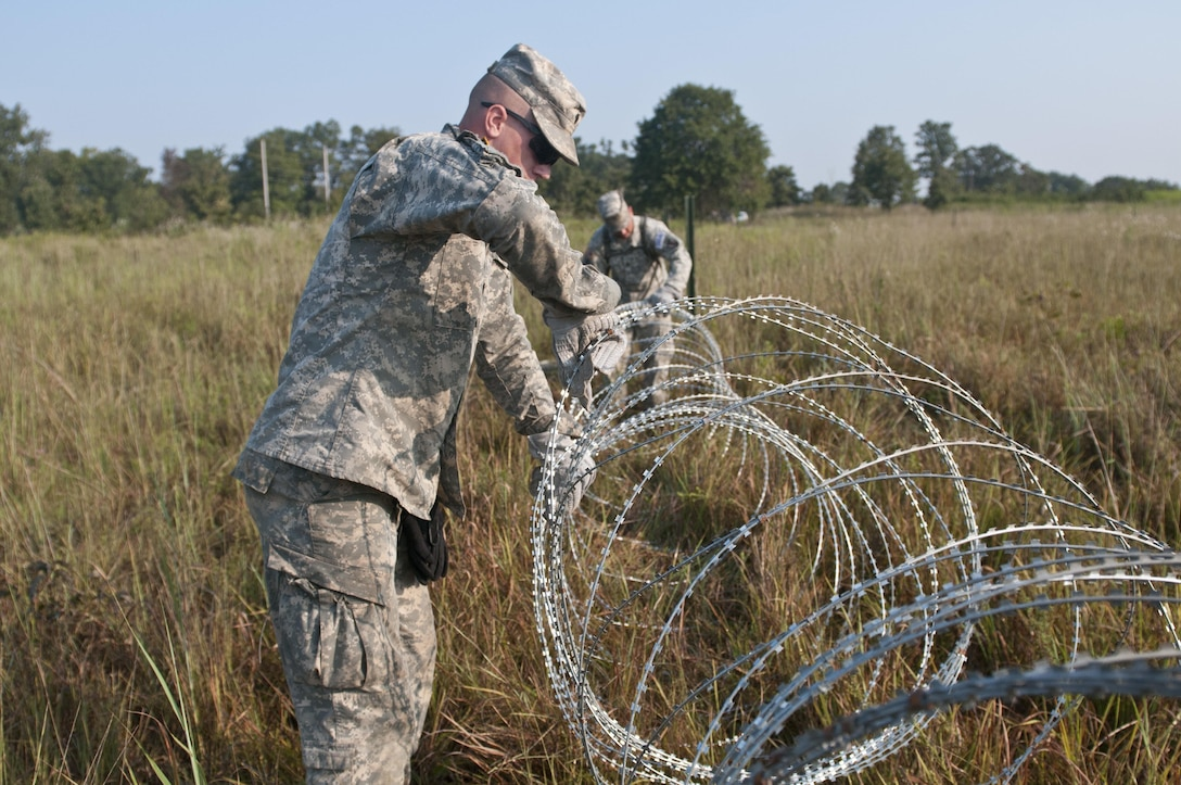 U.S. Army Reserve Soldiers with the 348th Engineer Company, lay concertina wire while emplacing a hasty frat fence during Sapper Stakes 2015 at Fort Chaffee, Ark., Sept. 1. (U.S. Army photo by Staff Sgt. Debralee Best)