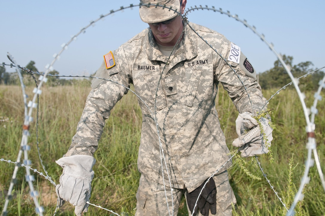 U.S. Army Reserve Spc. Ben Baumer, combat engineer, 348th Engineer Company separates concertina wire while emplacing a hasty frat fence as part of Sapper Stakes 2015 at Fort Chaffee, Ark., Sept. 1. (U.S. Army photo by Staff Sgt. Debralee Best)