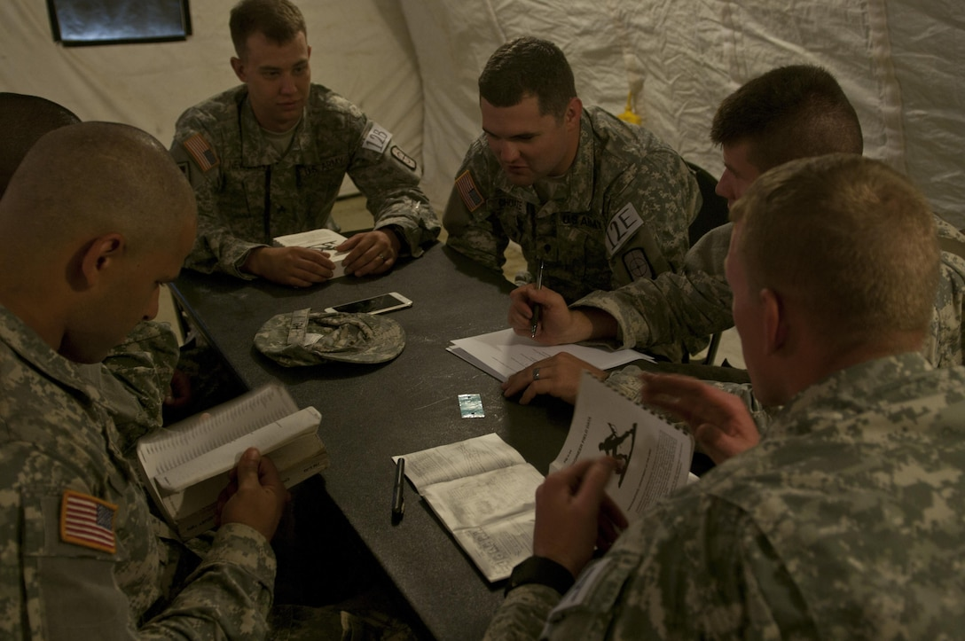 U.S. Army Reserve Soldiers from the 688th Engineer Company (Mobility Augmentation) out of Harrison, Ark., discusses test questions during the knowledge verification portion of Sapper Stakes 2015 at Fort Chaffee, Ark., Aug. 30. (U.S. Army photo by Staff Sgt. Debralee Best)