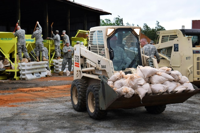 A soldier delivers a load of sandbags while guardsmen fill sandbags in anticipation of Hurricane Joaquin in Hephzibah, Georgia, Oct. 4, 2015. The Guardsmen are assigned to the 810th Engineer Company and 278th Military Police Company. Georgia Army National Guard photo by Capt. William Carraway