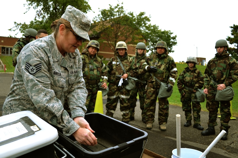 Staff Sgt. Alisa Garza, 111th Attack Wing's base civil engineering squadron emergency manager, explains decontamination techniques and entry and exit into various zones during Chemical, Biological, Radiological, Nuclear and Explosives survival training Oct. 3, 2015, at Horsham Air Guard Station, Pennsylvania. Garza demonstrated the procedures to Guardsmen donning their Mission Oriented Protective Posture gear who had just finished training with the M-50 joint service general purpose mask. (U.S. Air Force photo by Tech. Sgt. Andria Allmond/Released)