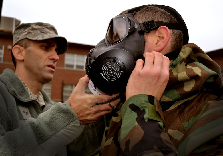 Senior Airman Christopher Feder, 111th Attack Wing's base civil engineering squadron emergency manager, helps a 111th Attack Wing Guardsman with his M-50 joint service general purpose mask during Chemical, Biological, Radiological, Nuclear and Explosives survival training Oct. 3, 2015, at Horsham Air Guard Station, Pennsylvania. The 111th Attack Wing members involved in the CBRNE survival training also received Self-Aid and Buddy Care training. (U.S. Air Force photo by Tech. Sgt. Andria Allmond/Released)