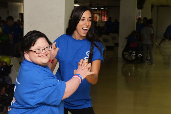 Staff Sgt. Kimberly Chroniak, 36th Maintenance Squadron, celebrates with a Special Olympics Guam athlete Oct. 3, 2015, at a bowling center in Tamuning, Guam. Service members dedicated eight weeks to coach participants for the event which included 125 athletes with intellectual disabilities. (U.S. Air Force photo by Senior Airman Joshua Smoot/Released)