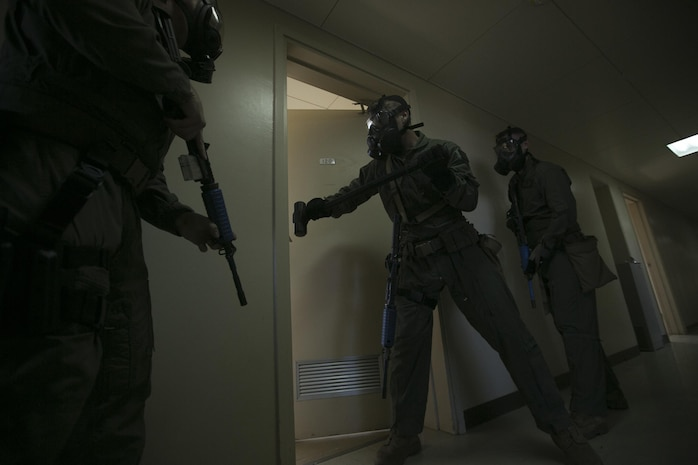 The Special Reaction Team breaches a barricaded door Sept. 23 during an active shooter exercise as part of Exercise Constant Vigilance 2015 aboard Camp Foster. SRT Marines swept through the building, clearing each floor room by room, ensuring no other threats were present before arriving at the shooter's barricade. SRT breached the barricade, detained the shooter and removed the hostage from the room. The Special Reaction Team responds to trouble calls such as active shooters with hostages in the same way the civilian special law enforcement teams act, according to Staff Sgt. Brandon Price, the section chief of the Special Reaction Team with the Provost Marshal's Office Headquarters and Support Battalion, Marine Corps Installations Pacific-Marine Corps Base Camp Butler, Japan.