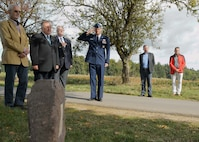 Col. Harry Benham, the U.S. Air Forces in Europe-Air Forces Africa operations and plans chief, salutes during the playing of taps during the revealing of a memorial stone for 2nd Lt. Priesley Cooper Jr. Sept. 25, 2015, in Dietingen, Germany. Cooper was conducting an escorting mission when his P-51D Mustang was shot down. The town of Dietingen buried him and 70 years later held a ceremony to honor him. (U.S. Air Force photo/Staff Sgt. Armando A. Schwier-Morales)