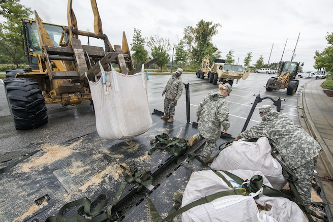 South Carolina Army National Guard soldiers deliver sandbags to the Columbia Riverfront Canal in an effort to repair the canal's breached levee in Columbia, S.C., Oct. 5, 2015. The South Carolina National Guard has been activated to support state and county emergency management agencies and local first responders as historic flooding impacts counties statewide. The soldiers are assigned to Company A, 218th Brigade Support Battalion. South Carolina National Guard photo by Air Force Tech. Sgt. Jorge Intriago