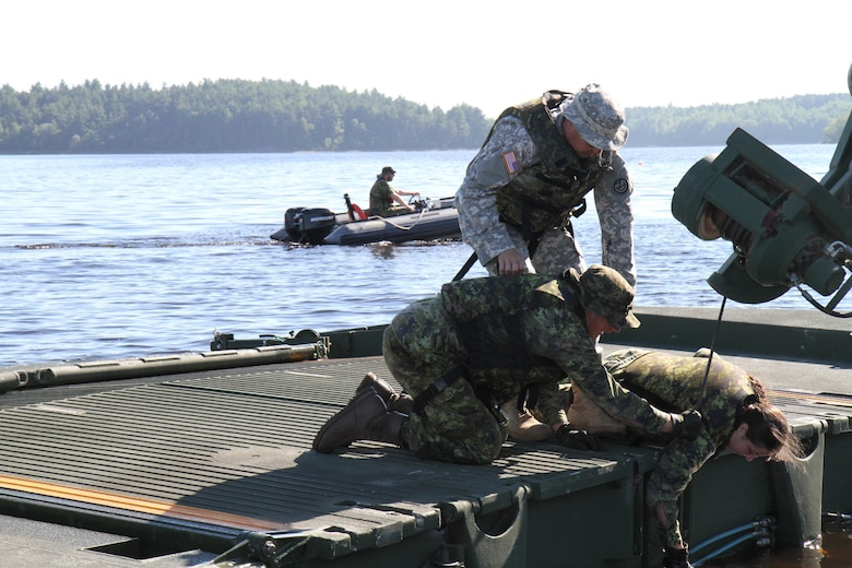 Sgt. 1st Class John Reyes of the Knoxville, Tenn., 1-100th Engineer Battalion helps instruct Canadian military engineer students as they learn to properly deploy a mobile floating bridge (MFB) during a training exercise at the Canadian Forces School of Military Engineering (CFSME) at Canadian Forces Base Gagetown in New Brunswick, Canada as part of an instructor exchange initiative between the U.S. and the CFSME, spearheaded by 1st Brigade Engineers out of Fort Leonard Wood, Mo.