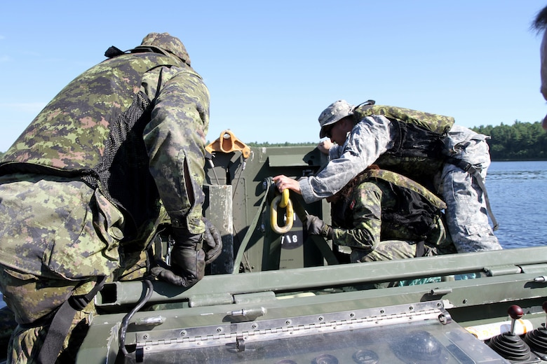 Sgt. 1st Class John Reyes of the Knoxville, Tenn., 1-100th Engineer Battalion helps Canadian military engineer students unhook and deploy a mobile floating bridge (MFB) during a training exercise at the Canadian Forces School of Military Engineering (CFSME) at Canadian Forces Base Gagetown in New Brunswick, Canada, as part of an instructor exchange initiative between the U.S. and the CFSME, spearheaded by 1st Brigade Engineers out of Fort Leonard Wood, Mo.