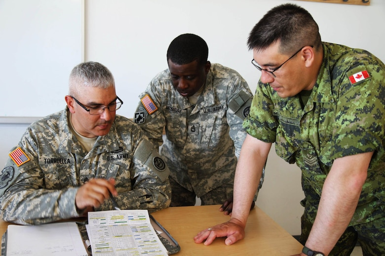 Sgt. 1st Class Hector Torruella of the 1st Battallion, 95th Engineer Regiment (1-95 EN) and Sgt. 1st Class Oniel Murray of the Fort Leonard Wood, Mo., 1st Brigade Engineers work with one of their Canadian counterparts while converting measurements to the metric system at the Canadian Forces School of Military Engineering (CFSME) at Canadian Forces Base Gagetown in New Brunswick, Canada, as part of an instructor exchange initiative between the U.S. and the CFSME, spearheaded by 1st Brigade engineers.