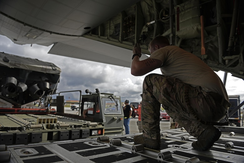 A 17th Special Operations Squadron MC-130J Commando II loadmaster, guides the driver of a load carrier toward an MC-130J Commando II during an exercise Sept. 18, 2015, at Andersen Air Force Base, Guam. The MC-130J was part of a dissimilar formation with an MC-130H that completed a Maritime Craft Aerial Delivery System airdrop.  This was the first time an MC-130J Commando II completed the MCADS airdrop in the Pacific.  (U.S. Air Force photo by Staff Sgt. Alexander Riedel)