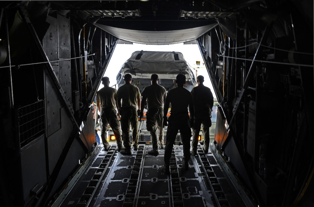 A team of MC-130 Combat Talon II loadmasters assigned to the 1st Special Operations Squadron stand ready to receive a load carrier approaching the aircraft during an exercise Sept. 18, 2015, at Andersen Air Force Base, Guam. The MC-130H was part of a dissimilar formation with an MC-130J that completed a Maritime Craft Aerial Delivery System airdrop.  This was the first time an MC-130J Commando II completed the MCADS airdrop in the Pacific.  (U.S. Air Force photo by Staff Sgt. Alexander Riedel)