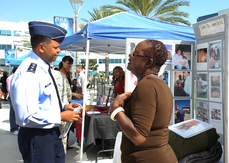 Lt. Gen. Samuel Greaves, SMC commander, talks with a representative from Cover the Homeless about her charity. The organization provides blankets, food clothing and transportation to homeless people in the Los Angeles area. (U.S Air Force photo by Van Ha)