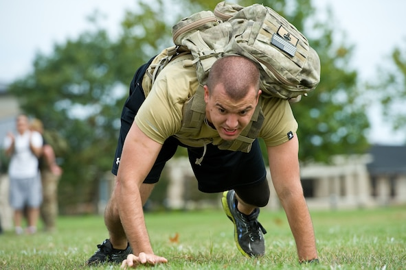 Senior Airman William Johnson, 436th Airlift Wing public affairs photojournalist, bear crawls during the GORUCK Light team cohesion challenge Sept. 25, 2015, on Dover Air Force Base, Del. Johnson, participating in his second GORUCK Light, was one of 31 participants that completed numerous physical challenges led by a qualified GORUCK Light cadre. (U.S. Air Force photo/Roland Balik)