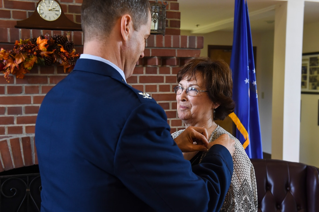U.S. Air Force Col. Thomas Dorl, 347th Rescue Group commander, fastens a retirement pin on Ruth Treadwell, 347th RQG secretary, during her retirement ceremony Oct. 1, 2015, at Moody Air Force Base, Ga. Throughout her career, Ruth worked as a secretary for 30 squadron commanders, 20 executive officers, and 10 group commanders. (U.S. Air Force photo by Senior Airman Ceaira Tinsley/Released)