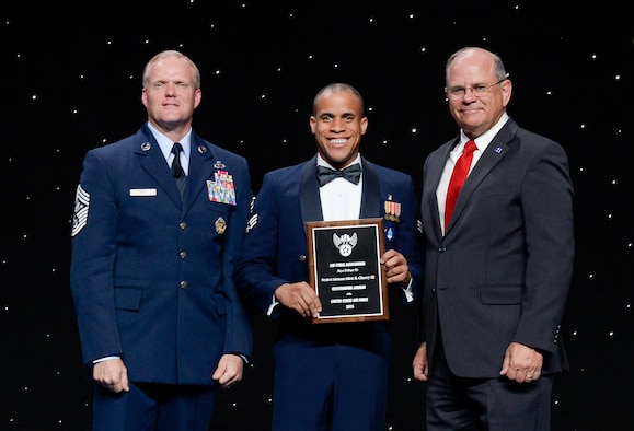 Chief Master Sergeant of the Air Force James Cody and Air Force Association Vice Chairman of the Board Scott Van Cleef flank Senior Airman Allen Cherry at an award ceremony during which Cherry is officially honored as a member of the 12 Outstanding Airmen of the Year, National Harbor, Md, September 14, 2015. (Air Force photo Andy Morataya)