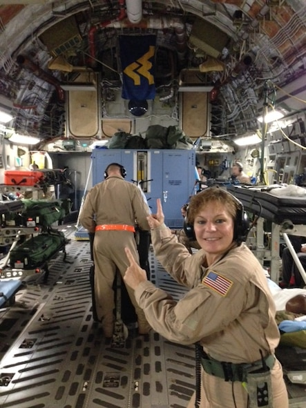 Tech. Sgt. Christine Cournoyer, an aeromedical technician with the 167th Aeromedical Evacuation Squadron based at the 130th Airlift Wing, Charleston, W.Va., proudly points to the Mountaineer flag while taking care of patients alongside a Wyoming Air National Guard AES crew. Cournoyer was the sole West Virginia Air National Guard aeromedical technician to fly aboard a C-17 Globemaster III piloted by a 167th aircrew during a recent aeromedical evacuation mission.