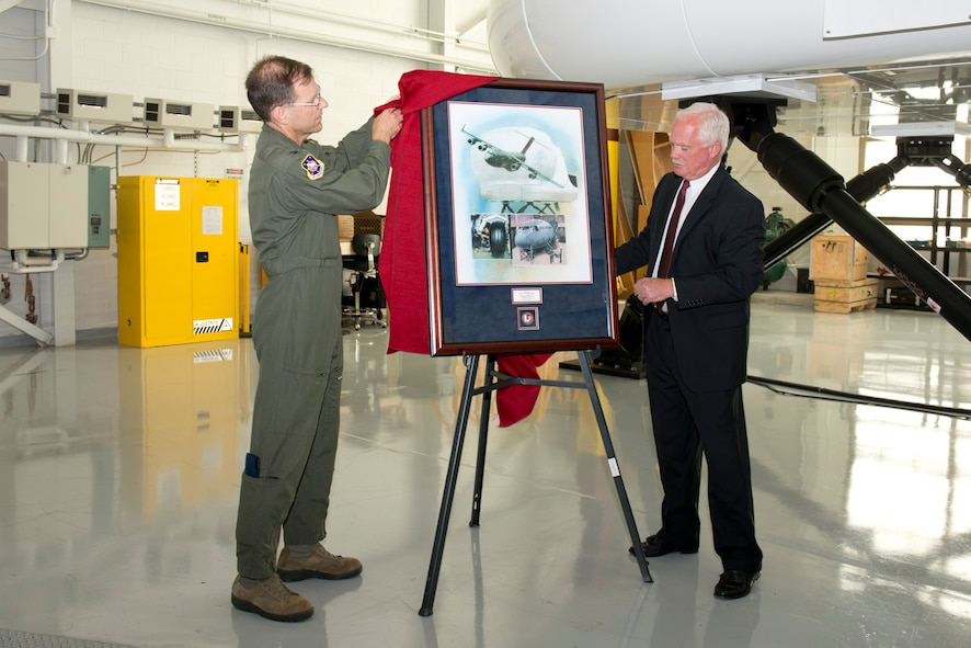 Col. Richard Robichaud, 167th Operations Group commander, assists Rodney Shrader, director of Air Force programs with L-3 Link Simulation and Training, with the unveiling of a framed print presented to the 167th Airlift Wing during the C-17 simulator training facility ribbon cutting ceremony, Sept. 24.(U.S. Air National Guard photo by Master Sgt. Emily Beightol-Deyerle/Released)