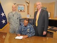 U.S. Navy Adm. Cecil D. Haney (center), U.S. Strategic Command commander, signs the 2015 USSTRATCOM Combined Federal Campaign kickoff letter at Offutt Air Force Base, Neb., Sept. 29, 2015. Prior to signing the document, Haney met with Paul Ross (right), the 2015 CFC chairman, and U.S. Air Force Maj. Trent Fausett, USSTRATCOM's 2015 CFC manager, to discuss this year's campaign, which officially begins Oct. 6 and runs until Dec. 15. CFC is the world's largest workplace giving program and partners with nonprofit, charitable organizations around the world, benefiting a wide range of causes. (USSTRATCOM photo by Steve Cunningham/Released)