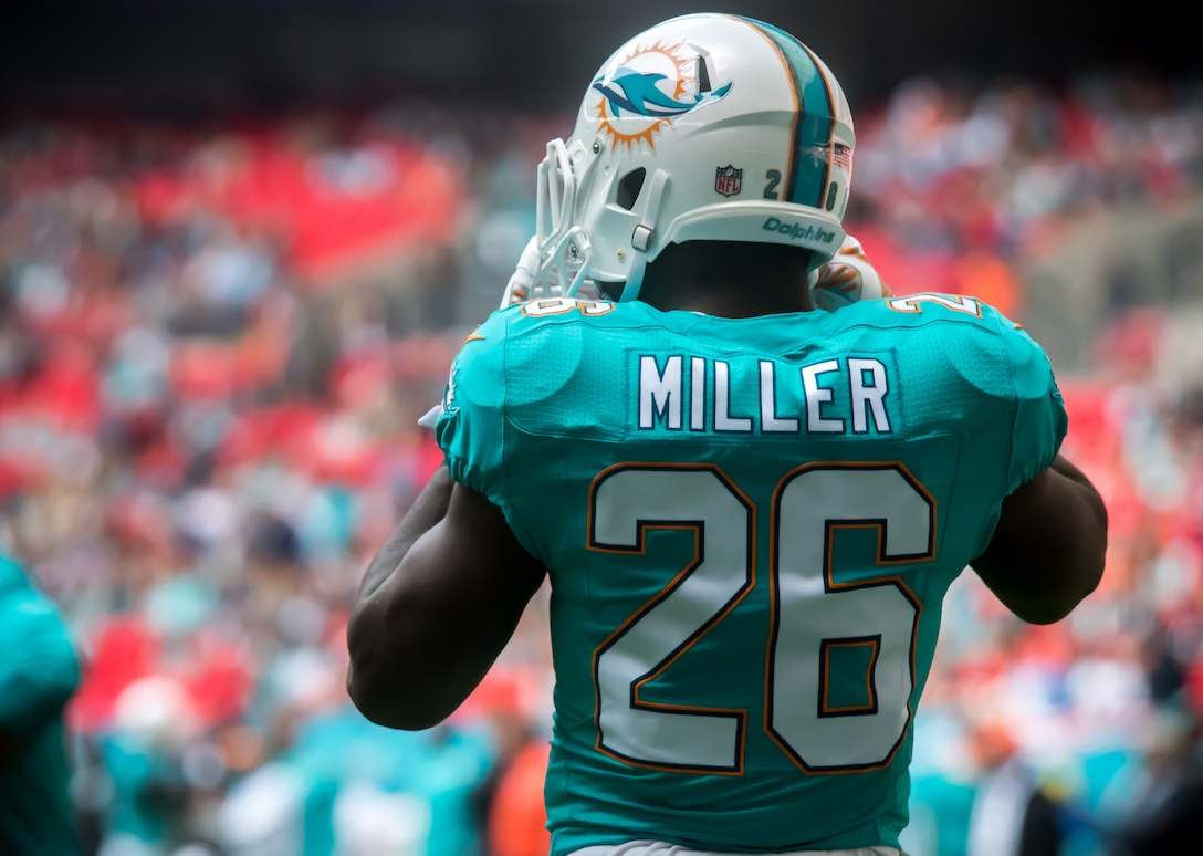 "Lamar Miller (26), Miami Dolphins running back, straps on his helmet before a play during the Miami Dolphins –New York Jets football game in London on Oct. 4, 2015. Miller says he has high praise for the troops overseas. ""I want to make sure those [service members] know that I appreciate all that they do for us."" (U.S. Air Force photo/Senior Airman Trevor T. McBride/Released)"