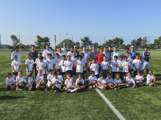 Japanese and American children, coaches and government officials pose for a picture the Japan-U.S. Friendship Kid's Soccer Event coordinated by the Chugoku-Shikoku Defense Bureau at the Suo-Oshima Town Athletics Track and Field in Yamaguchi Prefecture, Japan, Sept. 27, 2015. Twenty-five children from the station, ages 7-10, integrated with 20 Japanese children from schools in the local area to learn about each other's culture, do warm up drills and compete in a tournament. This soccer meet gave the opportunity for the children to interact, which helps strengthen the friendship between the Japanese and Americans.