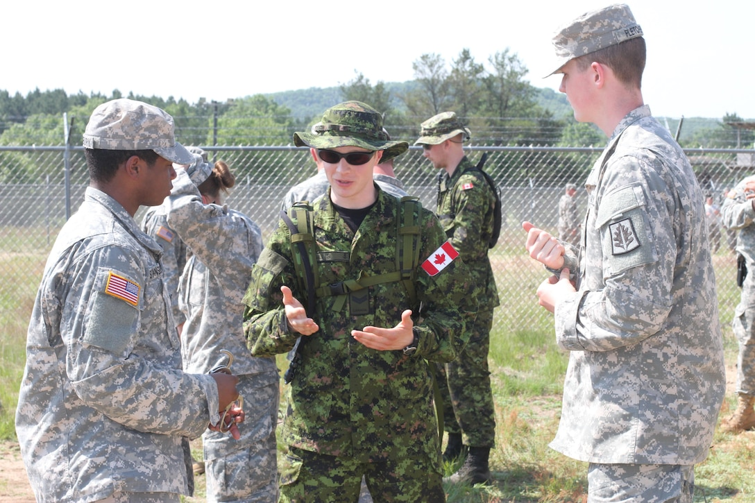 U.S. Army Reserve and Canadian soldiers discuss their distinctive detainee operations procedures before beginning the practical training during Operation Guardian Justice in Fort McCoy, Wis., June 9, 2015. (U.S. Army Reserve Photo by Spc. Stephanie Ramirez/Released)