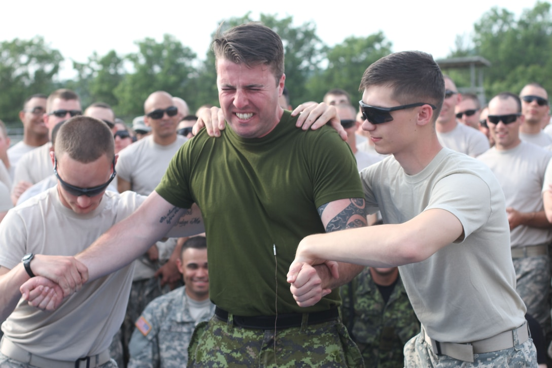 U.S. Army Reserve, and Canadian soldiers volunteer to feel the effects of the Taser after completing the practical portion of the Taser training during Operation Guardian Justice in Fort McCoy, Wis., June 10,2015. (U.S. Army Reserve Photo by Spc. Stephanie Ramirez/Released)
