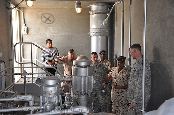 Defense Logistics Agency Director Air Force Lt. Gen. Andy Busch (right) listens to Royal Bahraini Air Force Lt. Col. Abdulla Abdullaare (second from right) during a May 17 tour of the Bahraini Air Force Fuel Pump House at Isa Air Base, Bahrain. May 17.