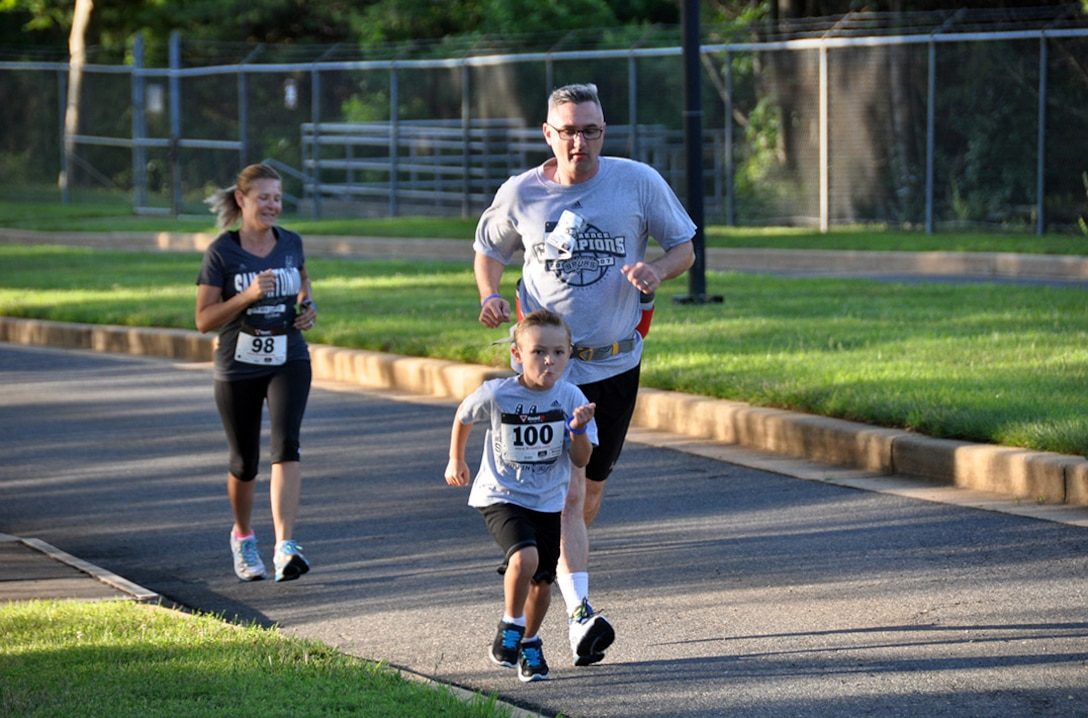 """FORT BELVOIR, Va. (June 24, 2015) Alex Absher, 5, races to beat his father, Defense Threat Reduction Agency employee Lennol Absher, during the """"fun"""" run/walk at the 2015 McNamara Headquarters Complex's Family Day June 24. More than 100 participants competed in the race, sponsored by the HQC Fitness Center."""
