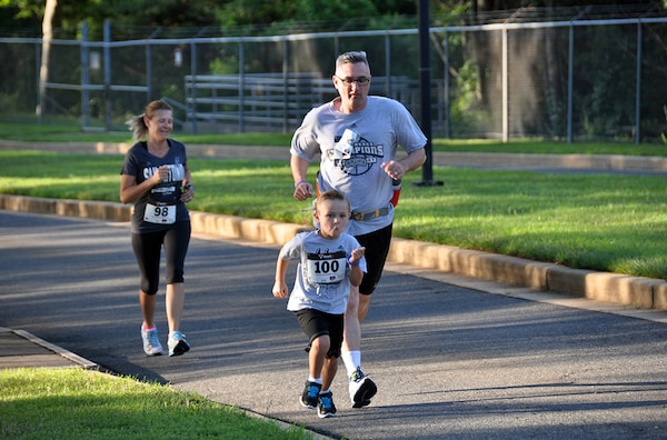 "FORT BELVOIR, Va. (June 24, 2015) Alex Absher, 5, races to beat his father, Defense Threat Reduction Agency employee Lennol Absher, during the ""fun"" run/walk at the 2015 McNamara Headquarters Complex's Family Day June 24. More than 100 participants competed in the race, sponsored by the HQC Fitness Center."