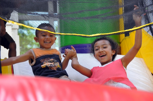 FORT BELVOIR, Va. (June 24, 2015) Seven-year-old Bianca Mata and 3-year-old brother Jeremiah hold hands while coming down a bounce house slide at the 2015 HQC Family Day June 24 at the McNamara Headquarters Complex. The annual event allows HQC employees to bring their families to work for fun and camaraderie.